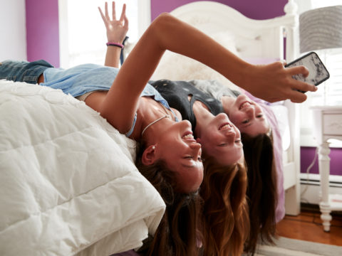 Three teen girls lay on a bed with their heads hanging off the side. They are playing on a smartphone